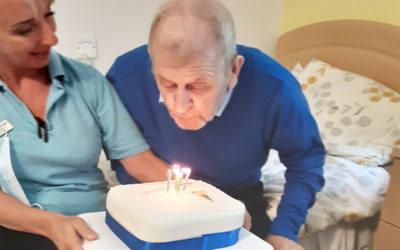 Woodstock Residential Care Home resident blowing out his birthday cake candles